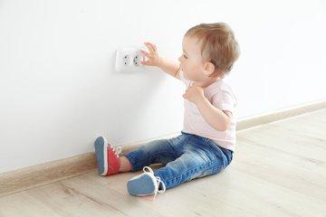 Bild von einem Kind an einer Steckdose